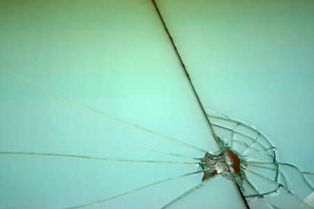 shatter: Detail of a broken glass in a green window