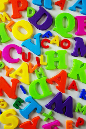 Composition of many colorful plastic toy letters over white background photo