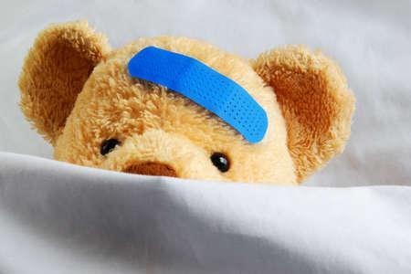 krankes kind: Foto von einem kranken Teddyb�r mit einem blauen Bandage im Bett