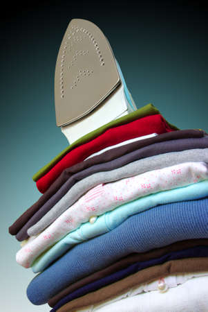 Pile of assorted clothes and iron against blue and black background. photo