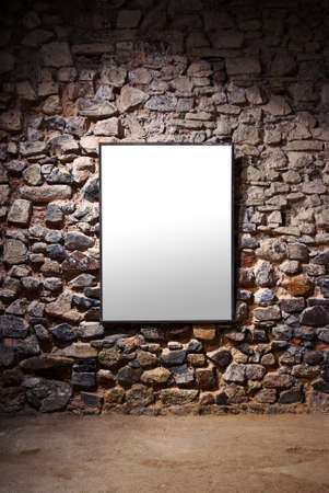 Empty frame attached to a stone wall in a gallery room photo