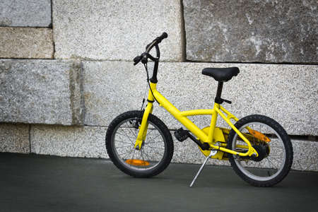 Single yellow bicycle on walkway against a stone wall Stock Photo - 4967044