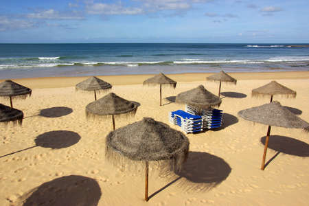 sunshades: Calm beach scene with straw sunshades and a pile of blue deckchairs Stock Photo