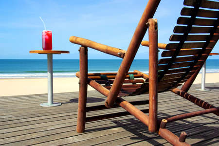 Detail of aconfortable chair and a cocktail on a table in the beach photo