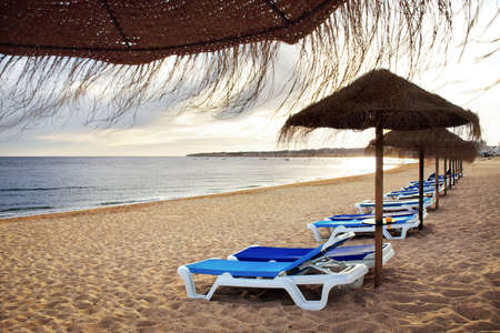 sunshades: View of straw sunshades, and blue deck-chairs in a beach