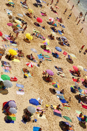 family outing: Birdseye view of a crowded beach in a hot summer day