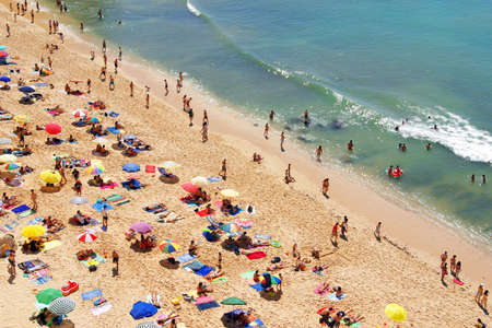 bathers: Birdseye view of a crowded beach in a hot summer day