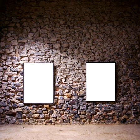 Two empty frames attached to a stone wall in a gallery room photo