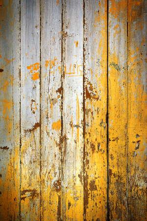 Background of old wooden door with peeling yellow paint photo