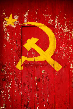 communistic: Communist Party symbol in a old wooden door with red paint peeling