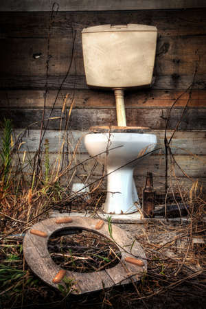 Photo of an old broken toilet cabin surrounded with wild vegetation