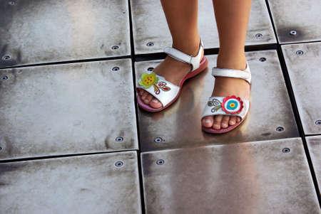 wearing sandals: Closeup on a girls feet wearing flowery white sandals over metallic floor