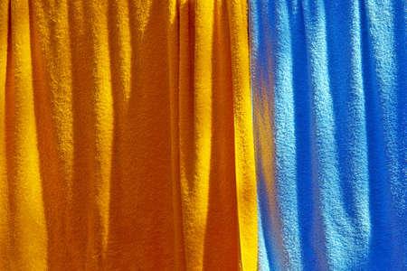 orange washcloth: Background of orange and blue towels hanged to dry