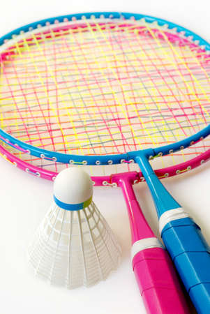 shuttlecock: Two colorful badminton rackets and a shuttlecock over white background Stock Photo