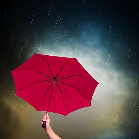 sotto la pioggia: Aperto ombrello rosa sotto il cielo scuro, con pioggia che cade