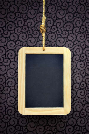 Writing slate hanged with a rope over a wallpaper with curly pattern Stock Photo - 5778875