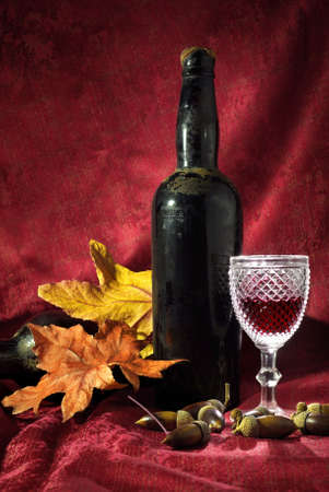 Vintage red wine glass and bottle with fall decoration details photo