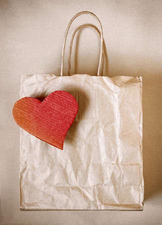 worn paper: Bolsa de papel desgastado con el coraz�n rojo de cart�n sobre papel de ajuste