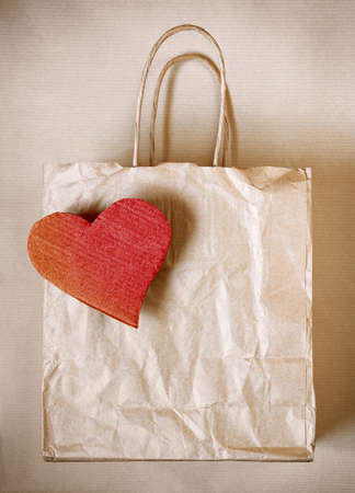 Worn paper bag with red cardboard heart over wrapping paper photo