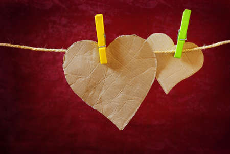 Heart-shaped cardboard pieces hanged in a rope with pins photo