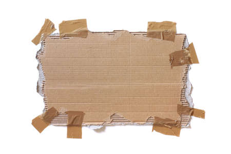 Piece of ripped cardboard stuck with tape isolated in white photo