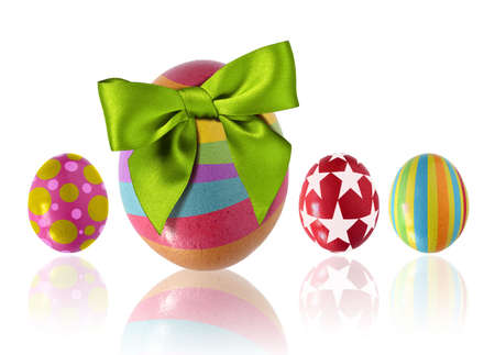 Big colorful easter egg with bow and three little ones by its side photo