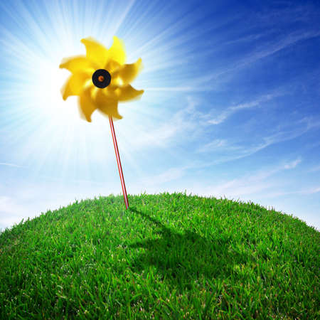 yellow, pinwheel on a round grass meadow at a bright sunny day photo