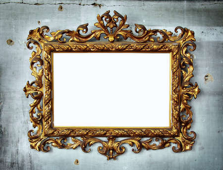 Beautiful golden baroque frame hanged in an old wall with holes and cracks photo