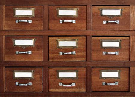 Filas de poco cajones con blancas etiquetas vacías en un módulo de muebles antiguos  Foto de archivo