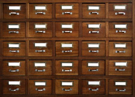 index card: Rows of little drawers with white empty tags in an old furniture module