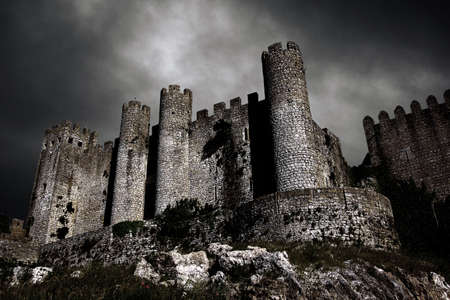 Disturbing scene with medieval castle at night with stormy sky Stock Photo