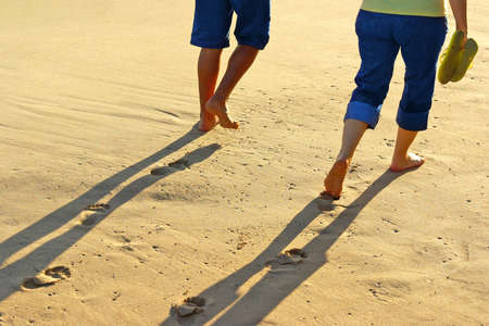 path to romance: Detail of the legs of a couple taking a walk in the sand