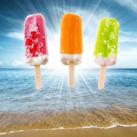 Three refreshing and colorful ice creams against a blue sky and sea