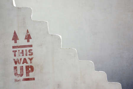 Detail of an old white stairway with the phrase This Way Up painted in red photo