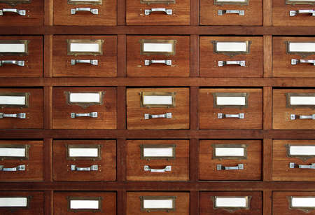 Rows of little drawers with white empty tags in an old furniture module photo