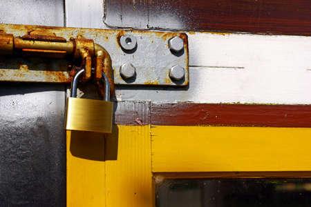 Close-up of a locked yellow door with a golden padlock Stock Photo - 7319976