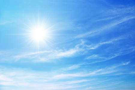 sky scape: bright blue sky with sun shining and some clouds Stock Photo
