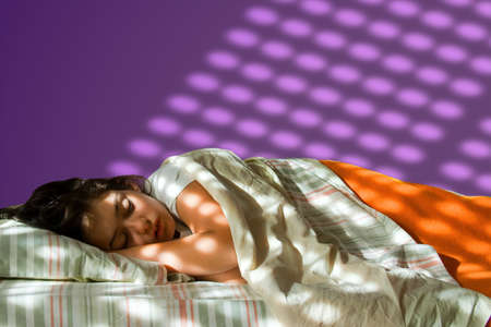 Young girl sleeping in her bed, with sunlignt projected in the purple wall Stock Photo - 7348865