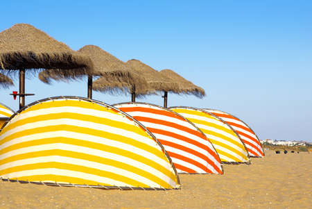 sunshades: Photo of colorful beach sun-shades and deck-chairs
