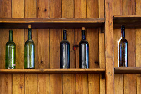 Fünf Weinflaschen ohne Bezeichnung in einem alten hölzernen Regal
