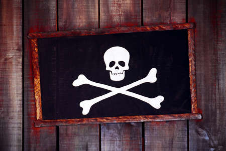 Framed pirate flag hanged in an old wooden wall  photo
