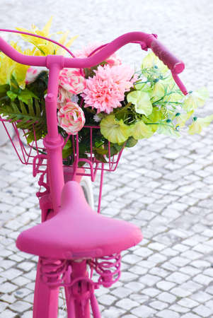 magenta flowers: Detail of a pink painted bicycle with a basket with flowers and leaves