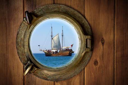 Nahaufnahme eines Bootes geschlossen Bullauge mit Blick auf eine alte Galeone Standard-Bild