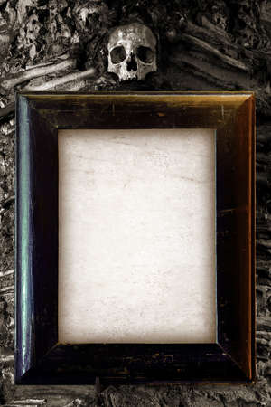 Old wooden frame and blank paper hanged on a wall with skull on top Stock Photo