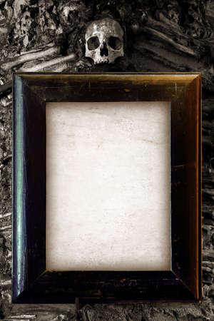 impiccata: Vecchio telaio in legno e carta bianca appeso su una parete con teschio in cima