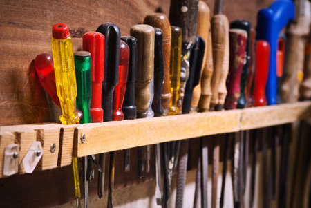 pegs: Row of old screwdrivers in a tool board of a garage