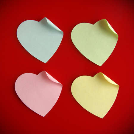 Background of four heart-shaped colorful post its over red photo