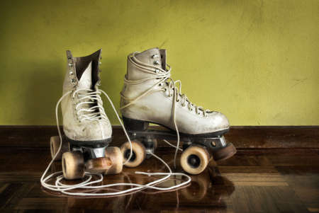 Old worn roller skates with big shoe-laces on a yellow wall background photo