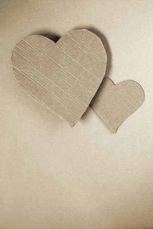 Two cardboard hearts over wrapping paper sheet photo