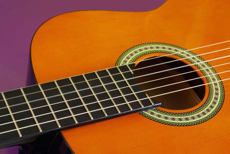 Closeup detail of a classic guitar over purple background photo